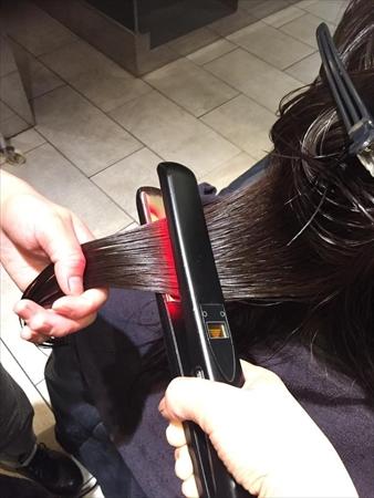 超音波の振動を生じさせるアイロンで、髪に塗った栄養剤を浸透
