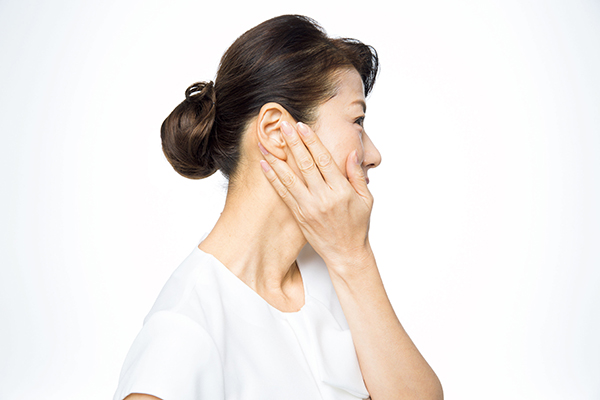 片手を反対側の耳からあご部分に軽く当てます。