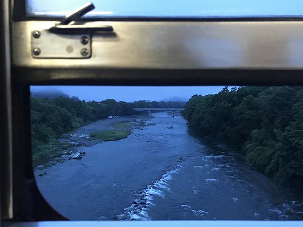 窓の隙間から写した朝靄のかかる荒川
