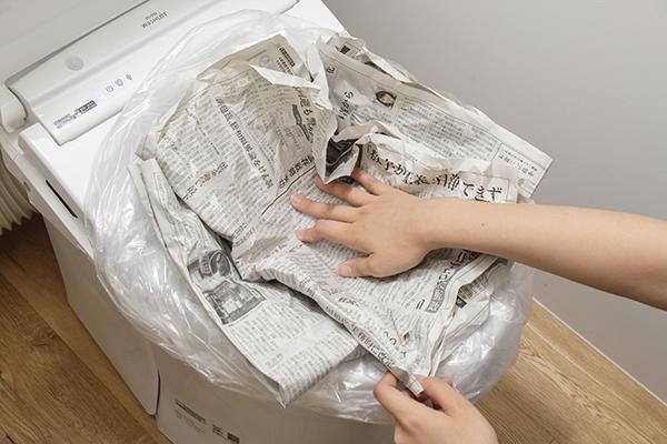 広げた新聞紙を2回たたみ、横と縦に重ねて便器に押し込む