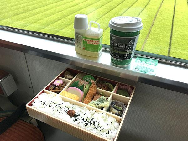 お茶畑を背景に、東海軒の特選幕の内弁当と、もみだし茶、大井川鐵道椀茶