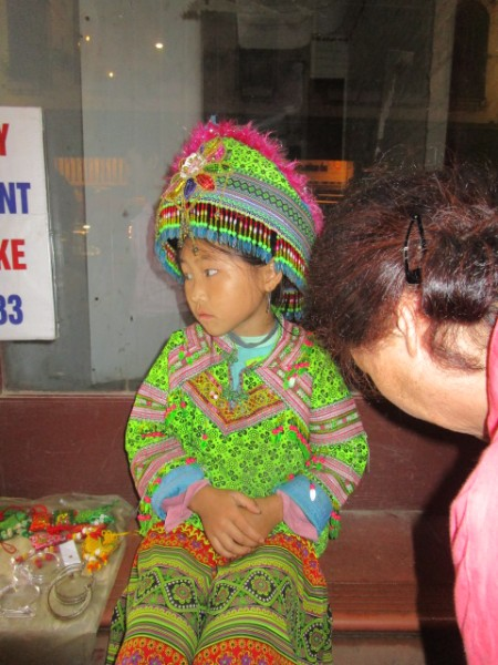 夜8時ごろ、気温が下がり寒さに震えながら民族衣装でみやげ物を売っている幼い女の子。
