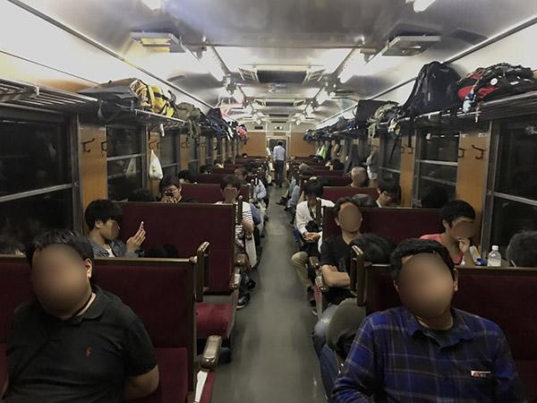 減光された車内で寝る乗客たち