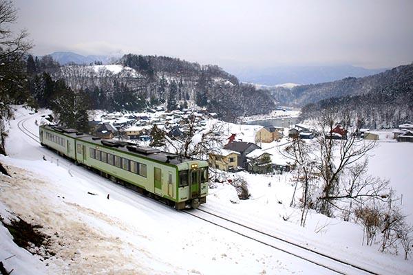 雪の飯山線を走る普通列車。撮影=坪内政美