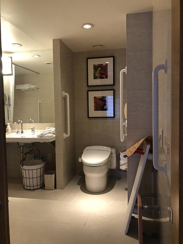 ユニバーサルルームのバス、トイレの例。段差がなく、洗面台の足元の空間が広い。